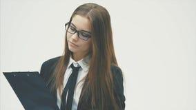 Uma menina do negócio que veste um dobrador do documento e um sorriso amigável está estando em um fundo branco vídeos de arquivo