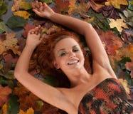 Uma menina do redhead está encontrando-se nas folhas de outono fotos de stock royalty free