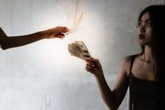 Uma menina do toxicômano está dando o dinheiro dos dólares a um traficante de drogas para o buyin fotografia de stock royalty free