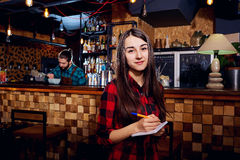 Uma menina do trabalhador do garçom toma uma ordem na barra do café imagens de stock