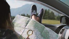 Uma menina do turisk olha um mapa usando uma lente de aumento ao sentar-se em um carro e ao colar seus pés para fora a janela con filme
