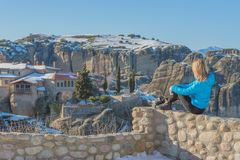 Uma menina do viajante senta-se altamente contra as rochas do monastério de Meteora em Grécia em um dia ensolarado brilhante imagem de stock