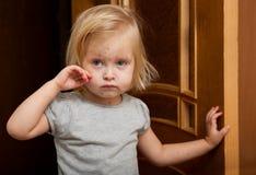 Uma menina doente está perto da porta fotografia de stock royalty free