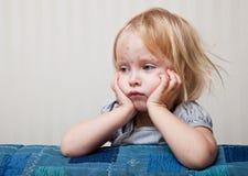 Uma menina doente está sentando-se perto da cama imagens de stock royalty free