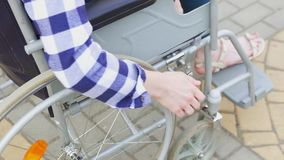 Uma menina dos enfermos que senta-se em uma cadeira de rodas O ` s obteve-lhe as mãos na roda vídeos de arquivo