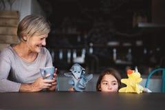 Uma menina e uma avó pequenas com fantoches em casa Fotografia de Stock Royalty Free