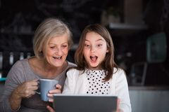 Uma menina e uma avó pequenas com tabuleta em casa Imagens de Stock Royalty Free
