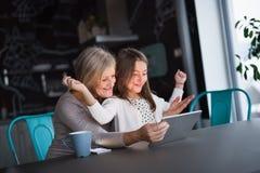 Uma menina e uma avó pequenas com tabuleta em casa Imagem de Stock