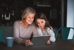 Uma menina e uma avó pequenas com tabuleta em casa Foto de Stock