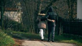 Uma menina e uma caminhada de Guy Embraced a rua com um cão vídeos de arquivo