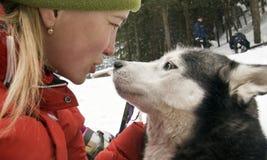 Uma menina e seu cão de puxar trenós Foto de Stock Royalty Free