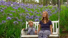 Uma menina e seu filho que balançam em um grande balanço em um parque bonito dos amantes na cidade de Dalat filme