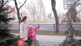 Uma menina e sua mãe estão andando em torno da cidade do inverno e estão falando alegremente video estoque