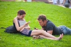 Uma menina e um homem novo que descansam no gramado Imagens de Stock