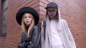 Uma menina e um indivíduo estão levantando na cidade com uma parede de tijolo no fundo Olham a câmera no estilo filme