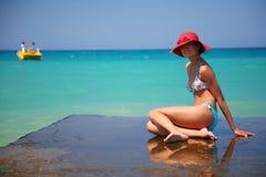 Uma menina e um mar do azure Fotos de Stock Royalty Free