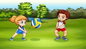 Uma menina e um menino que jogam o voleibol Fotografia de Stock