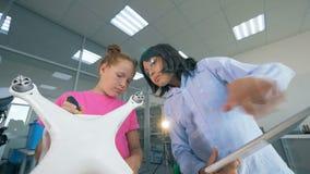 Uma menina e um trabalho do menino em um laboratório, reparando o UAV, zangão filme