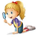 Uma menina e uma lente de aumento Fotos de Stock
