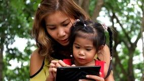 Uma menina e uma mãe asiáticas estão jogando o jogo engraçado na tabuleta vídeos de arquivo