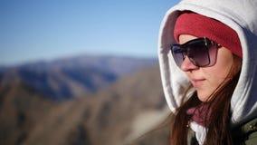 Uma menina em óculos de sol pretos e em uma capa está sobre a montanha e admira a vista movimento lento, 1920x1080, completamente filme