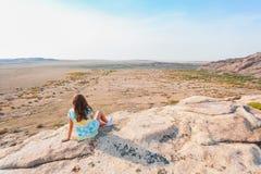 Uma menina em uma camisa colorida senta-se em uma rocha na perspectiva do horizonte foto de stock