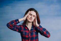 Uma menina em uma camisa de manta torceu sua cara na dor e levanta suas mãos para sua cara foto de stock royalty free