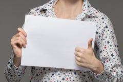 Uma menina em uma camisa guarda uma folha de papel branca nas mãos e na mostra imagem de stock