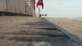 Uma menina em uma camisa vermelha anda em um assoalho de madeira na areia video estoque