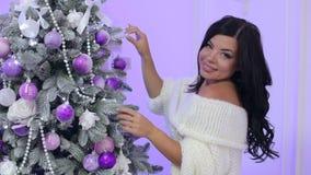 Uma menina em uma camiseta decora uma árvore de Natal filme