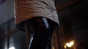 Uma menina em caneleiras pretas, em sapatilhas e em um revestimento longo atravessa a cidade da noite Fim acima A c?mera move-se  vídeos de arquivo