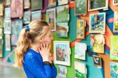 Uma menina em uma exposição das pinturas, apreciando vendo a arte moderna imagens de stock