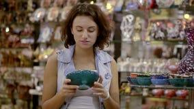 Uma menina em uma loja de lembrança oriental Uma morena agradável escolhe uma lembrança de uma viagem ao leste filme