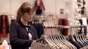 Uma menina em uma loja de roupa escolhe uma camiseta video estoque
