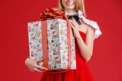 Uma menina em meias listradas com um sorriso guarda um close-up em um fundo vermelho fotos de stock royalty free