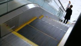 Uma menina em sapatas leves e na roupa preta vem nas etapas da escada rolante e desce Líquidos de limpeza das mulheres na parte i filme