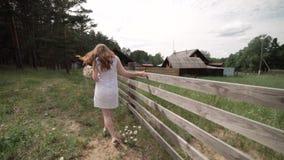 Uma menina em um branco sarafan com um ramalhete em suas mãos está andando ao longo de uma cerca de madeira filme
