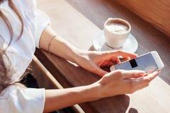 uma menina em um café bebe o café e usa o Internet no Smart-telefone Local de trabalho em um café Foto de Stock