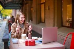 Uma menina em um café exterior com um portátil que fala a alguém com uma chamada video, guardando a cutelaria em suas mãos fotografia de stock