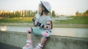 Uma menina em um capacete e em uma defesa patina em patins de rolo A criança rola nos rolos no parque A menina aprende filme