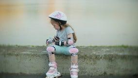 Uma menina em um capacete e em uma defesa patina em patins de rolo A criança rola nos rolos no parque A menina aprende vídeos de arquivo