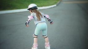 Uma menina em um capacete e em uma defesa patina em patins de rolo A criança rola nos rolos no parque A menina aprende video estoque
