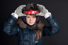 Uma menina em um capacete e em óculos de proteção do esqui Foto de Stock Royalty Free