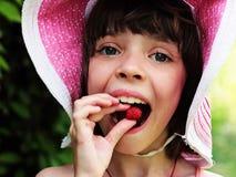 Uma menina em um chapéu está comendo framboesas Foto de Stock Royalty Free