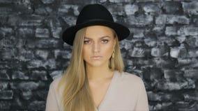 Uma menina em um chapéu negro e em uma camisa cinzenta que levantam contra um fundo da parede de tijolo video estoque