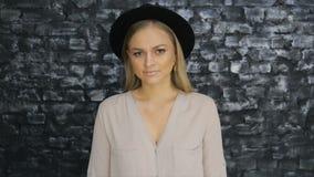 Uma menina em um chapéu negro e em uma camisa cinzenta que levantam contra um fundo da parede de tijolo filme