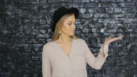Uma menina em um chapéu negro e em uma camisa cinzenta que levantam contra um fundo da parede de tijolo vídeos de arquivo
