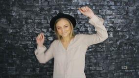 Uma menina em um chapéu negro está dançando no fundo de uma parede textured video estoque