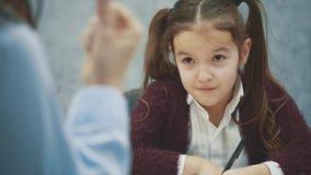 Uma menina em um fundo cinzento escreve trabalhos de casa Durante esta mamã discutirá e acenando seu conceito do punho das relaçõ video estoque