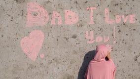 Uma menina em um hijab cor-de-rosa com giz escreve no paizinho da parede eu te amo filme